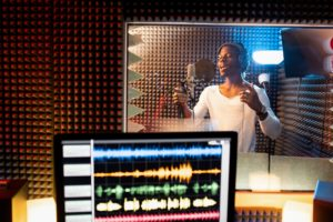 Young man of African ethnicity singing in microphone in sound recording studio