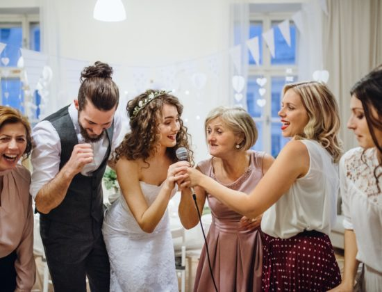 A young bride with other guests dancing and singing on a wedding reception.
