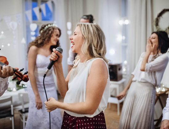 A young woman singing on a wedding reception, bride and guests dancing.