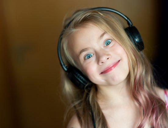 Natural light portrait of beautiful girl listening music in headphones .Charming girl in black earph