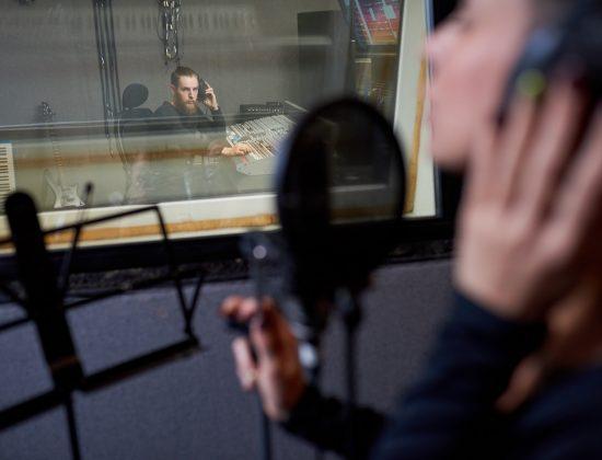 Operator working with singer in studio